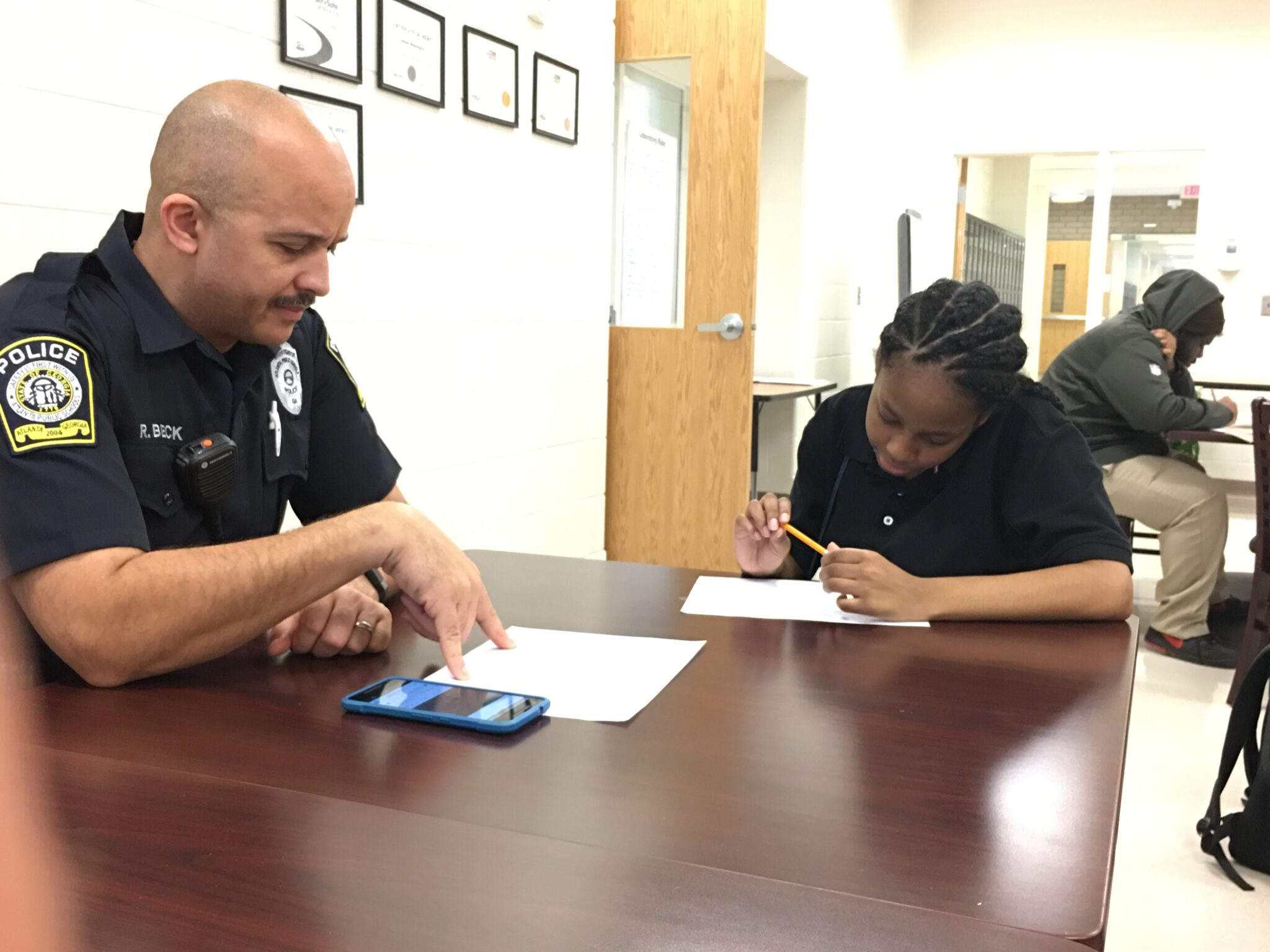 Student writing with a police officer